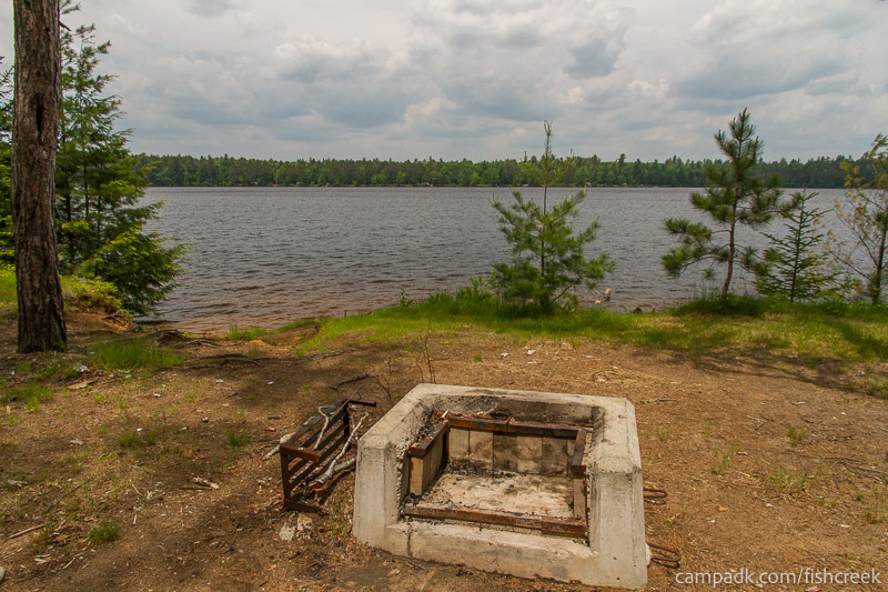 Campsite Photo of Site 200 at Fish Creek Pond Campground, New York - Fireplace View