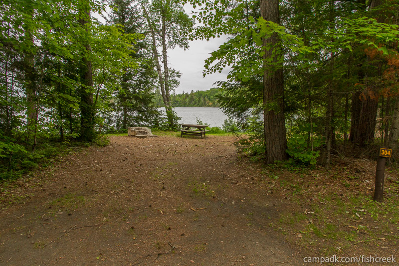 Campsite Photo of Site 304 at Fish Creek Pond Campground, New York - Looking at Site from Road Sign Visible